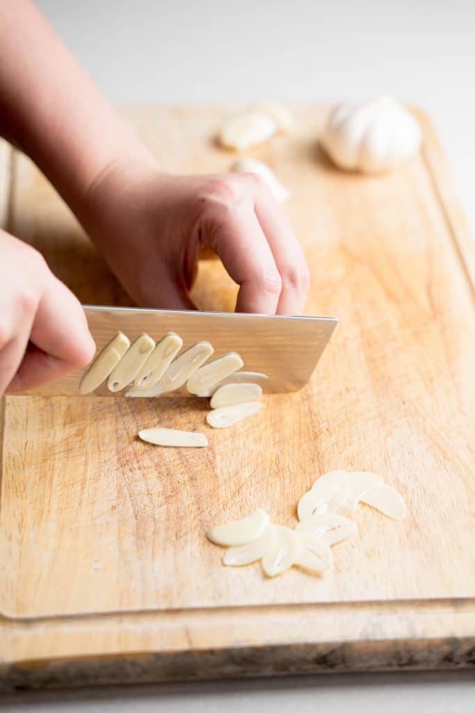 Knife slicing garlic clove thinly on a wood cutting board