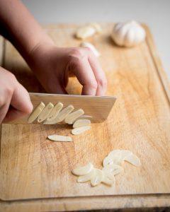 Thinly slicing garlic on a wood cutting board