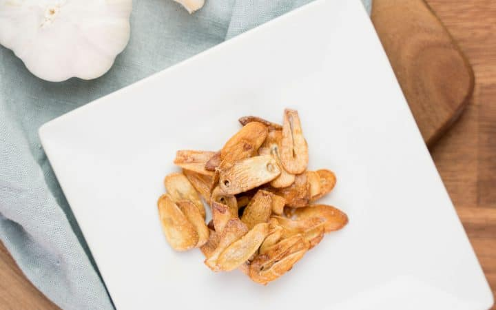 Baked garlic chips on a white plate with a linen napkin and a head of garlic