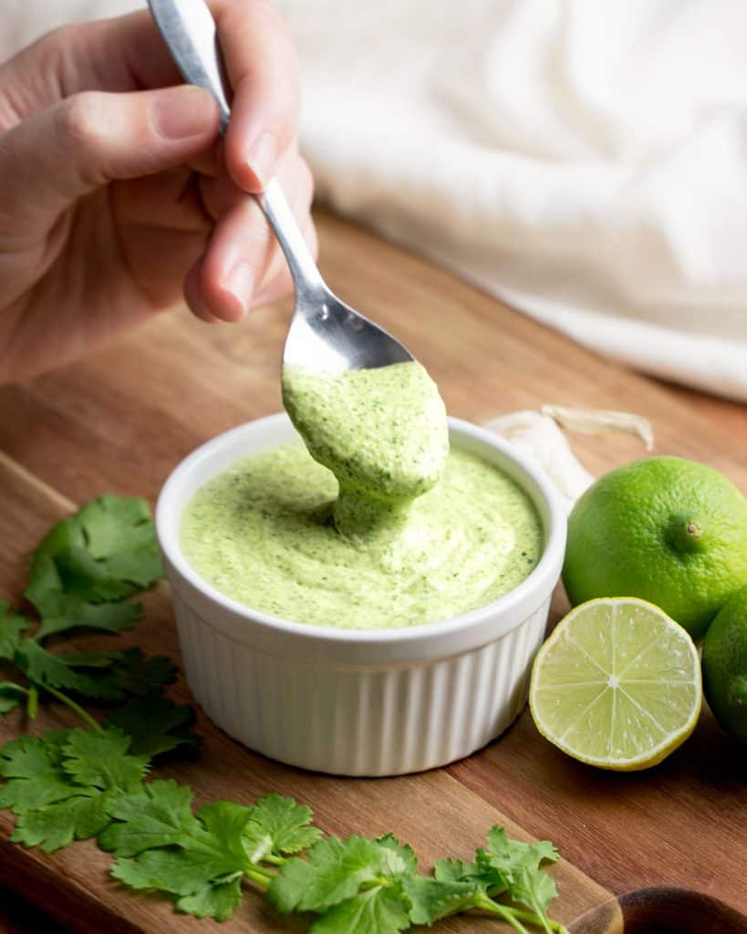 Spoon scooping sauce out of a ramekin with cilantro and limes around it