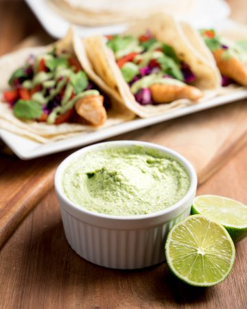 Ramekin of cilantro sauce with fish tacos in the background