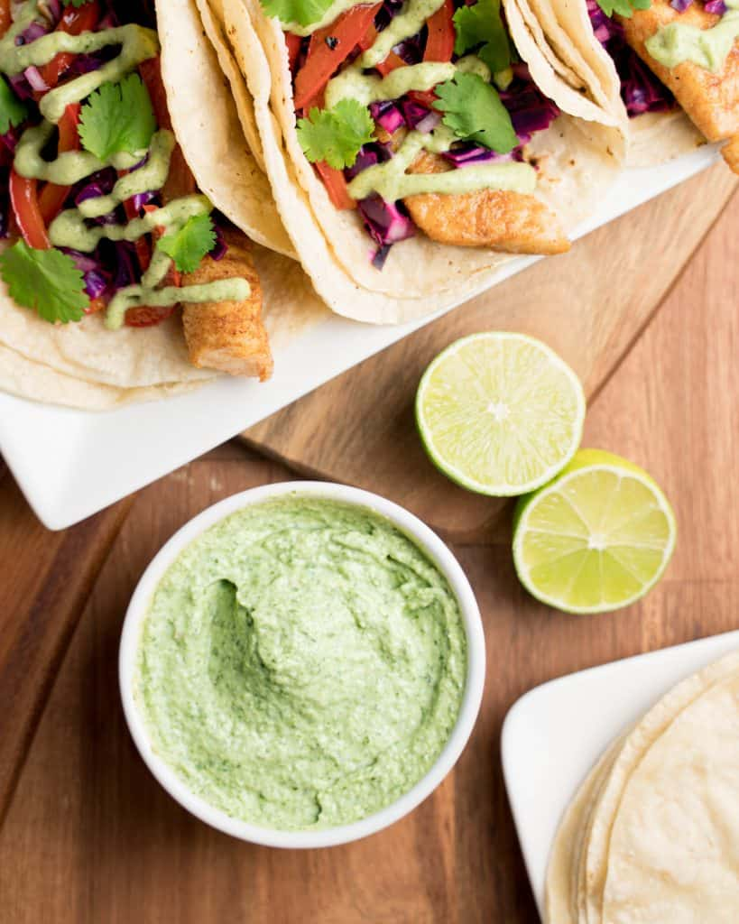 Ramekin of cilantro sauce with limes, tortillas, and fish tacos around it