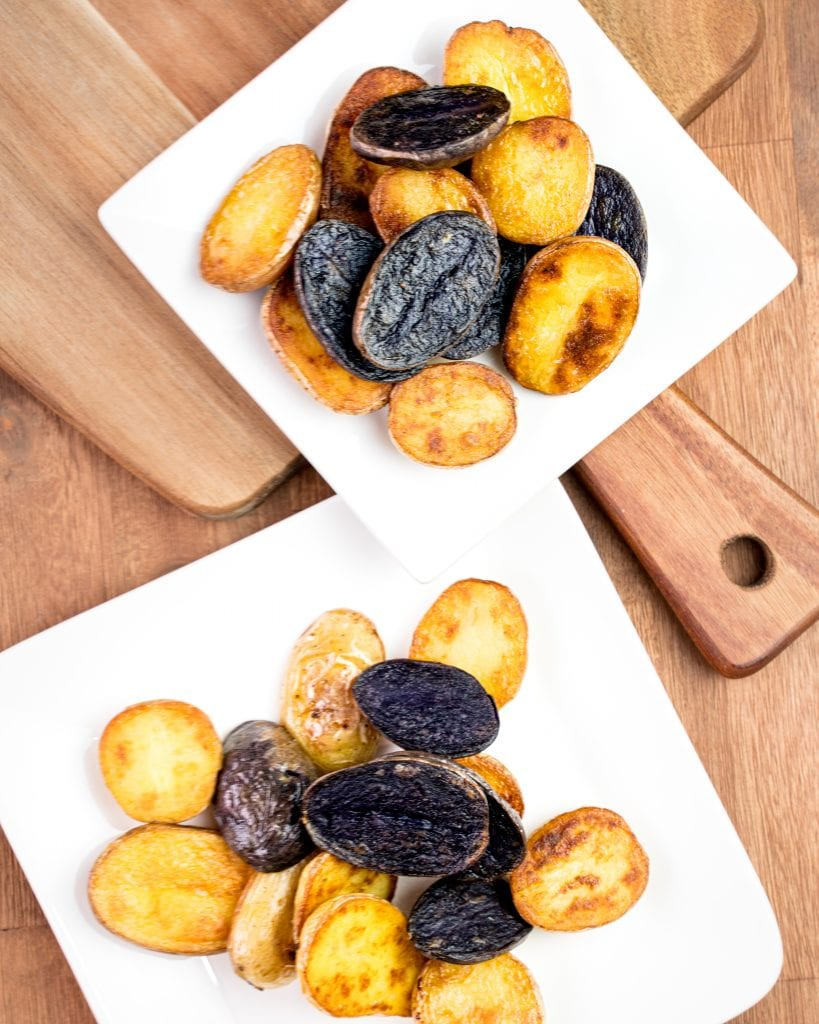 Two plates of confit potatoes on a wood surface