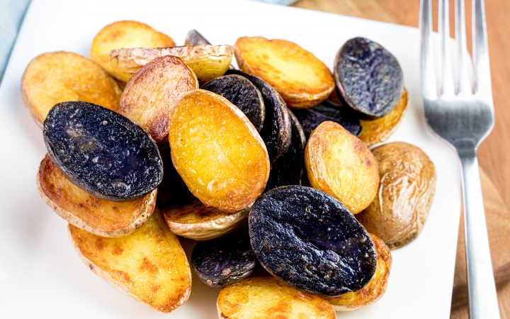Plate of confit fingerling potatoes on a wood cutting board with a fork and blue linen napkin