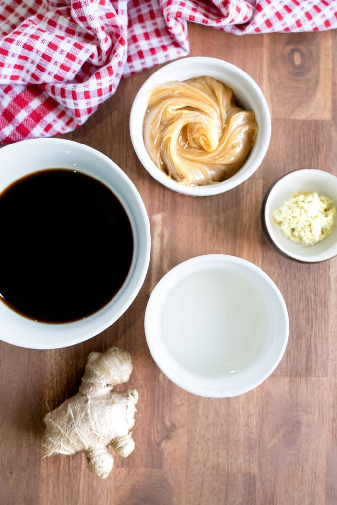 Overhead view of bowls of ingredients for honey teriyaki sauce on a wood surface