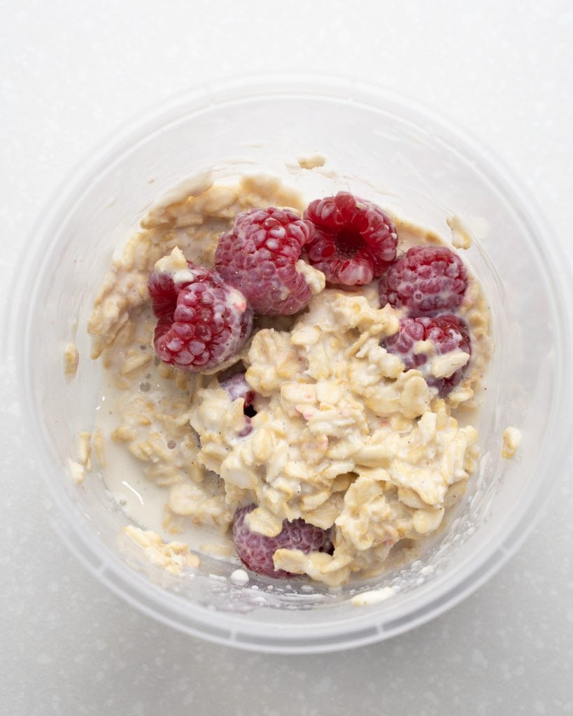 Overhead view of a jar of stirred overnight oats using fresh raspberries.
