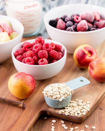 Assortment of ingredients for overnight oats on a wood cutting board, including oats, nectarines, fresh and frozen berries, and milk