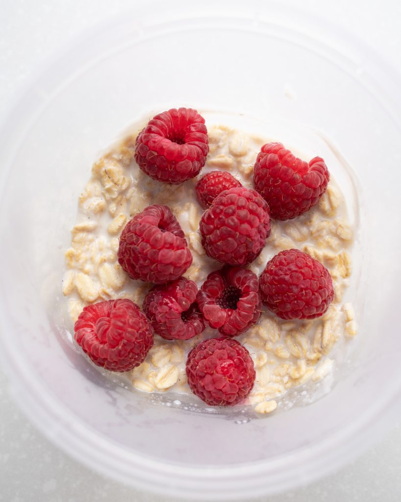 Overhead view of a jar of overnight oats using fresh raspberries before stirring.