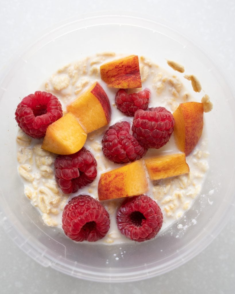 Overhead view of a jar of overnight oats using fresh raspberries and nectarines.