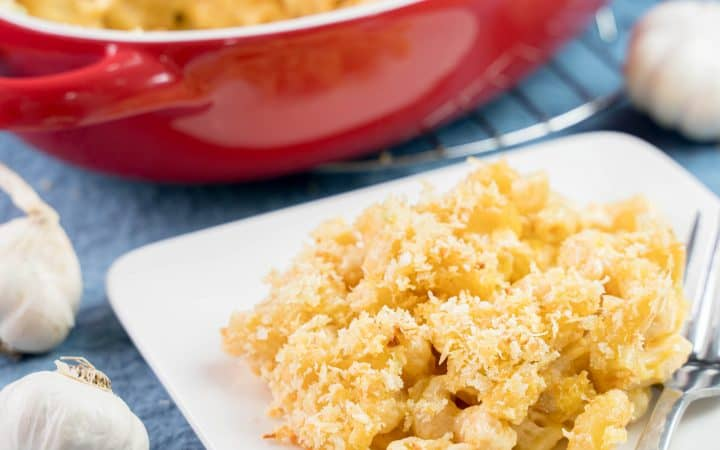 Plate of garlic Parmesan mac and cheese with a baking dish holding the rest in the background