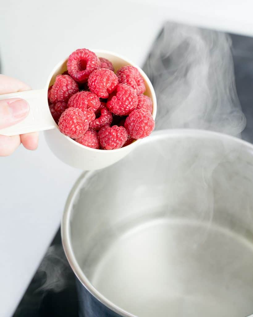 Hand pouring raspberries from a measuring cup into a pot.