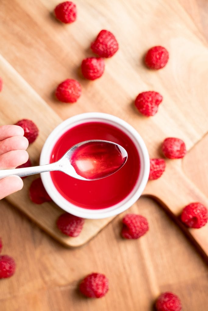Overhead view of spoon holding bright red raspberry syrup over a bowl, with raspberries scattered around