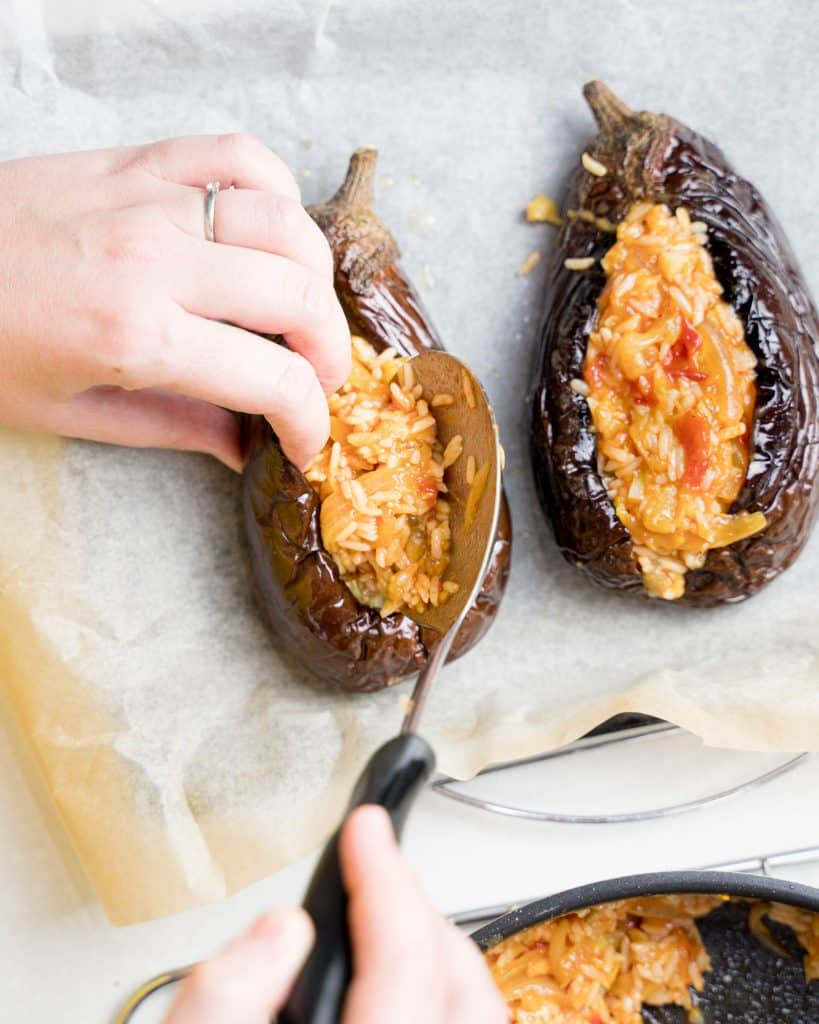 Overhead view of stuffing an eggplant with rice mixture, with another stuffed eggplant in view