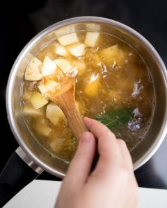 Stirring a pot of soup with potato chunks