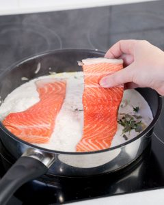 Hand placing salmon into a pan of simmering coconut milk
