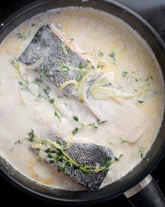 Salmon poaching in pan of coconut milk, skin-side up