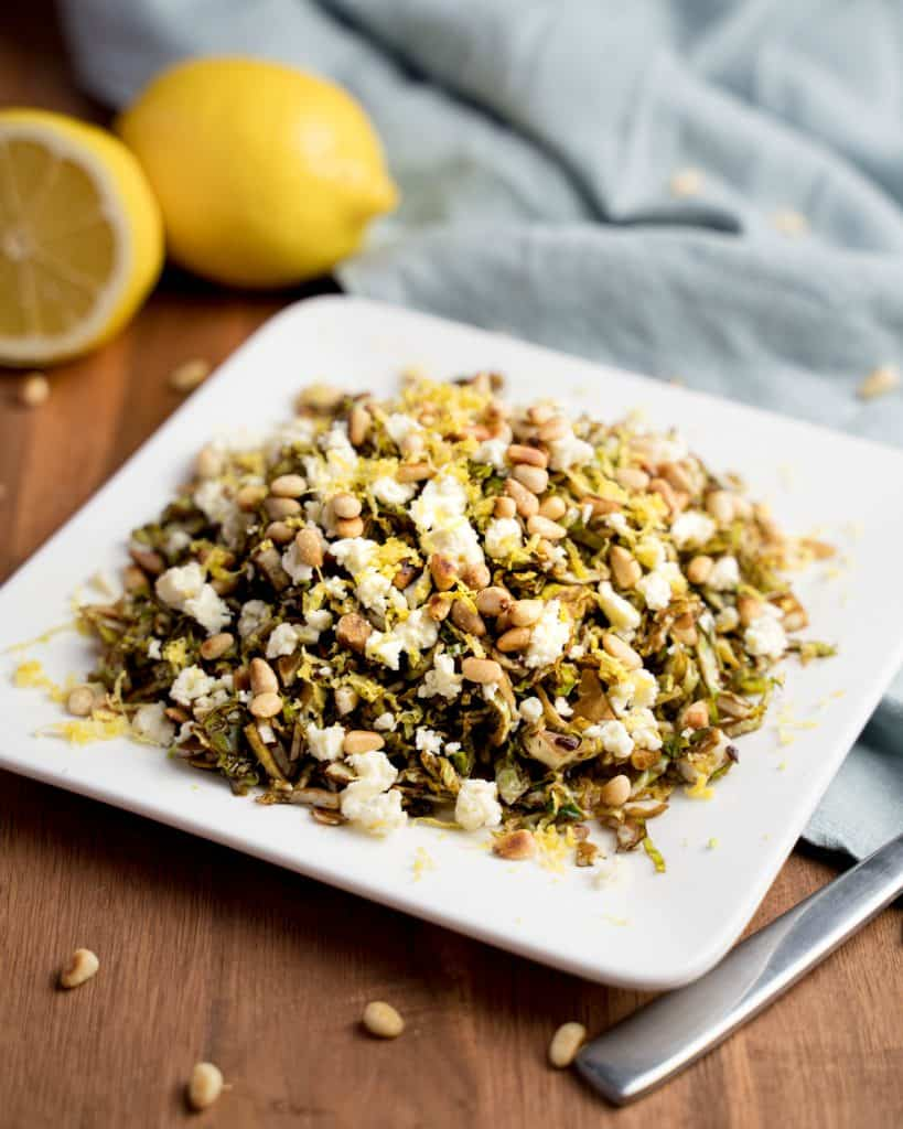 Plate of shredded Brussels sprouts with balsamic vinegar, feta, pine nuts, and lemon