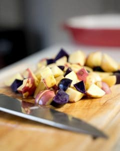 Chunks of colorful potatoes on a wood cutting board