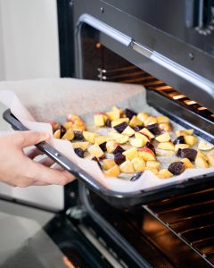 Putting a baking sheet of potato chunks into the oven