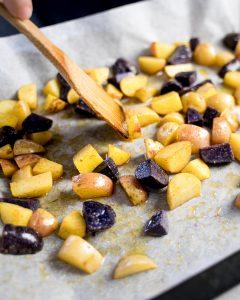 Partially roasted potato chunks on a baking sheet