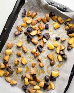 Roasted potato chunks on a baking sheet