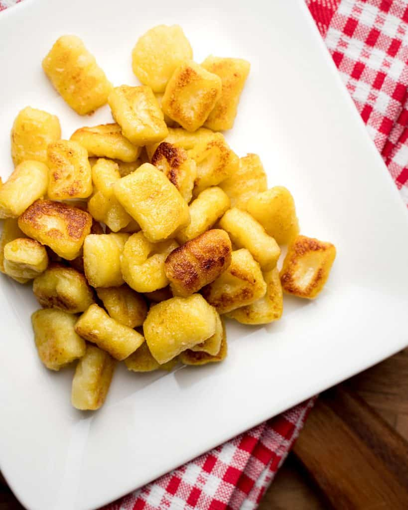 Overhead view of white plate of vegan potato gnocchi without sauce