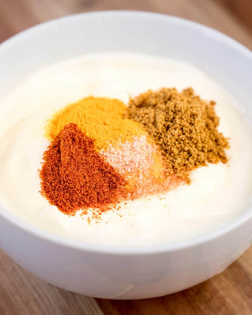 Bowl of yogurt with several spices and salt poured on top