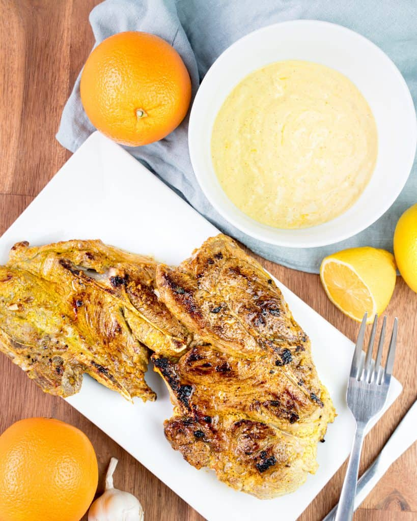 Overhead view of lamb chops on a plate with oranges and lemons around and a bowl of marinade