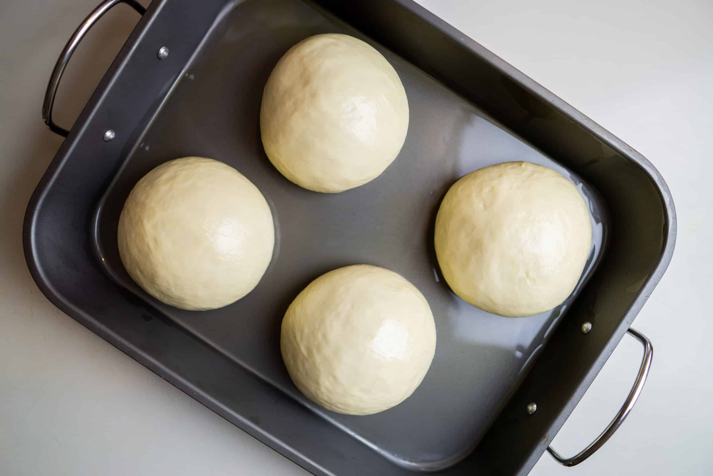 Make great pizza at home without any special tools by proving dough in a roasting tray.