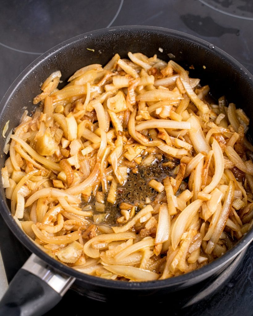Pan on the stove full of cooked sliced fennel, onion, and garlic